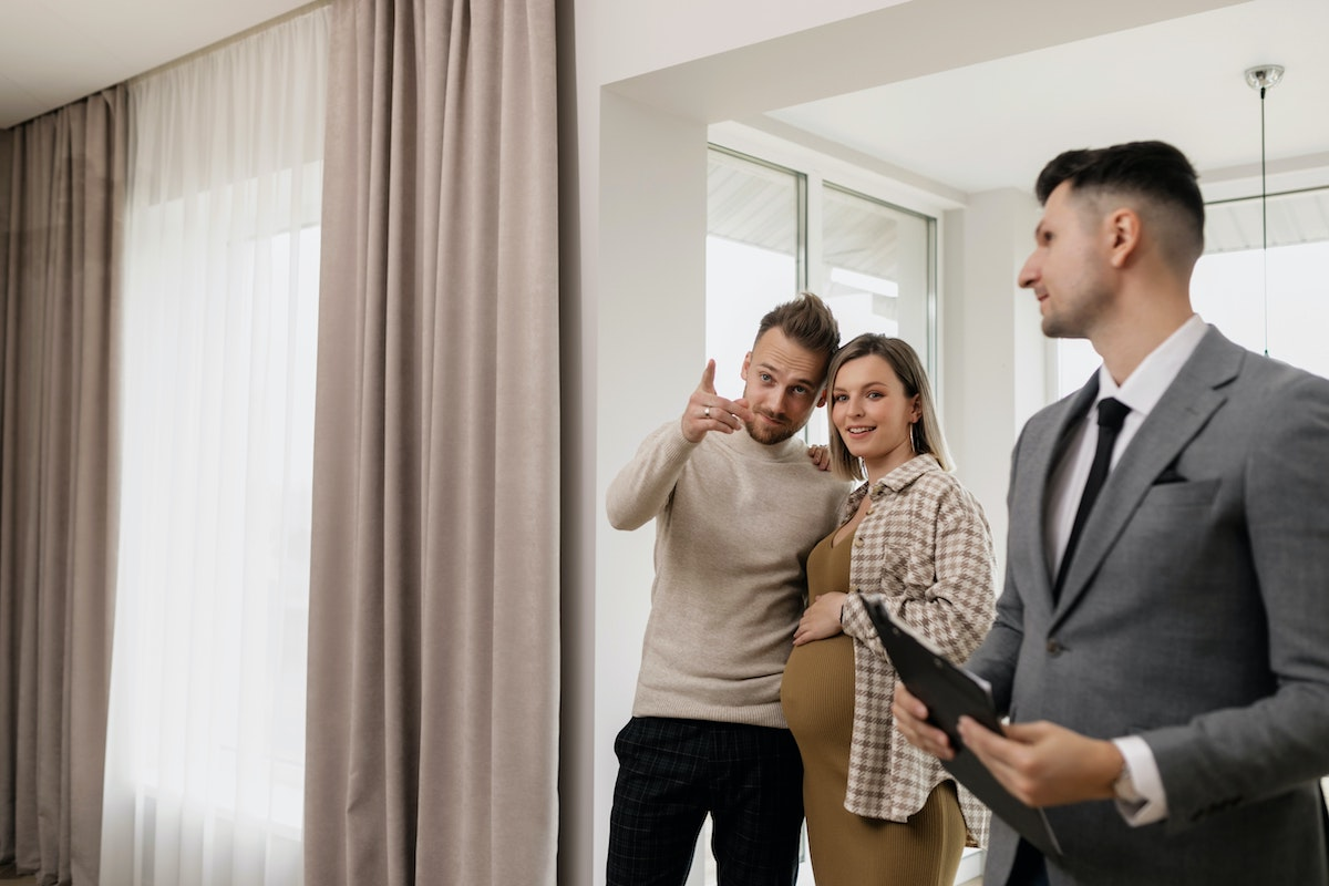 couple inspecting a house with a realtor